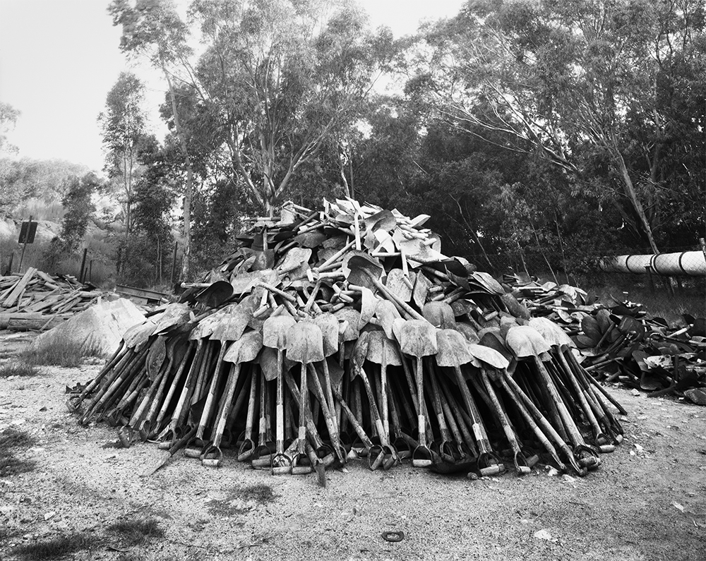 'Lashing' shovels retrieved from underground. Every grain of sand in the yellow tailings dumps that made the Witwatersrand landscape and every grain of gold that made its wealth, came from a rock off a black man's shovel underground. Central Salvage Yard, Randfontein Estates, Randfontein, 1966  1966 silver gelatin photograph on fibre-based paper Image courtesy Goodman Gallery, Johannesburg and Cape Town © The David Goldblatt Legacy Trust