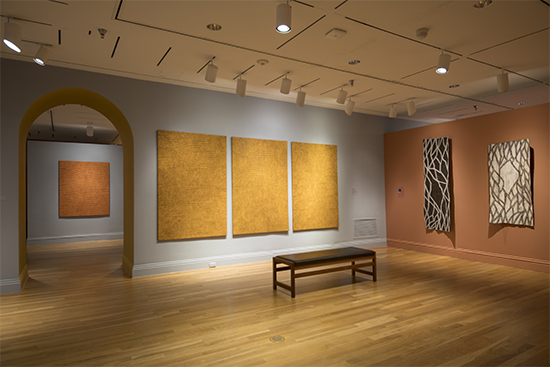Showing, on the left, four synthetic polymer paint on canvas works by Yukultji Napangati and, on the right, two bark paintings by Nonggirrnga Marawili. (Photo by Lee Stalsworth)