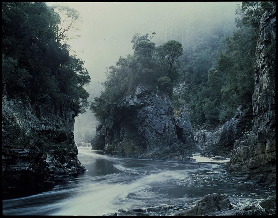 Peter Dombrovskis Australia, 1945 -96 Morning Mist, Rock Island Bend, Franklin River  1979,  printed 2019 Epsom inkjet print on Canson Baryta Prestige 340gsm  paper, with 10mm KapaMount (exhibition copy) / 63.5 x 86.3cm (sheet); 66.3 x 89 (frame) Courtesy of National Library of Australia and Es tate of  Peter Dombrovskis .