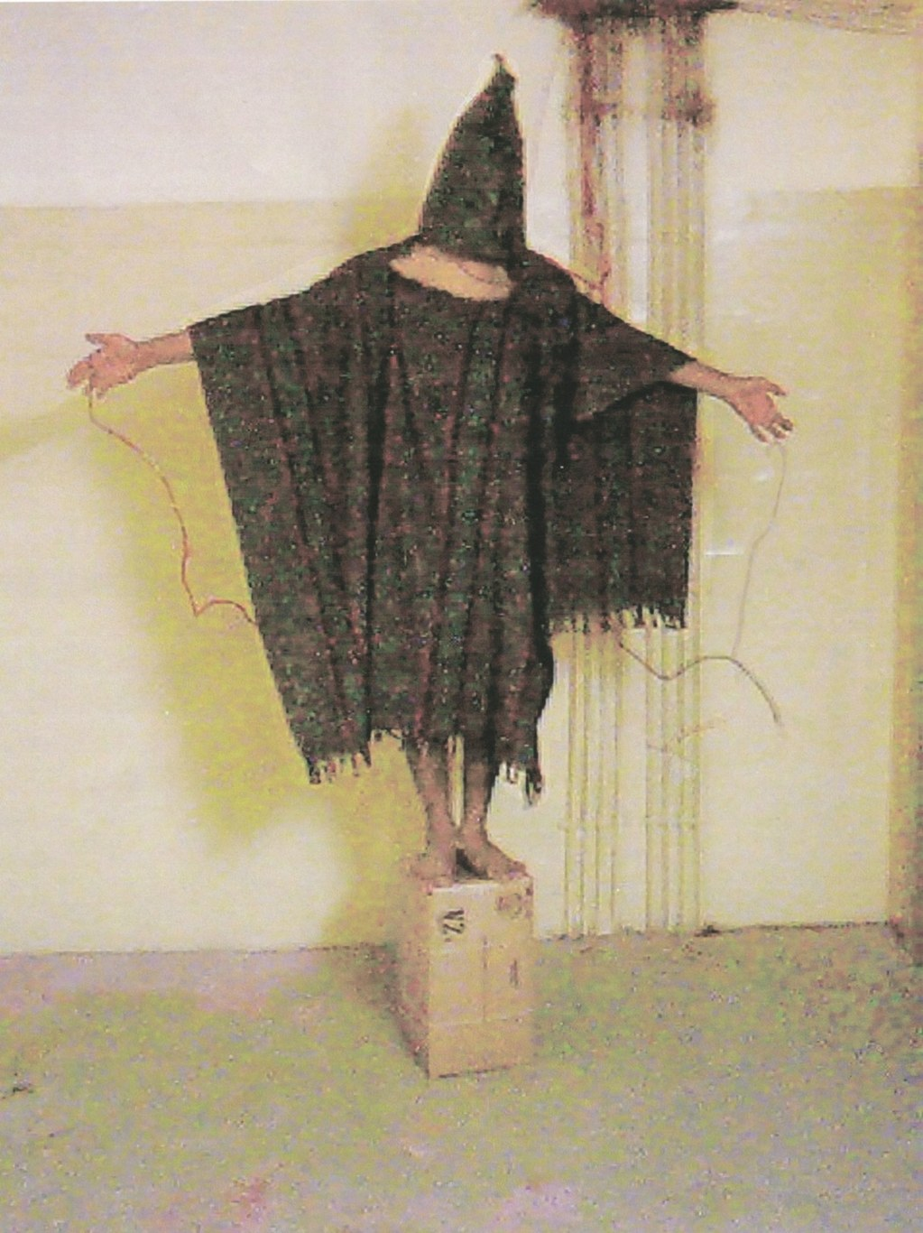 11:01 p.m., Nov. 4, 2003. Detainee with bag over head, standing on box with wires attached. This is one of Staff Sgt. Ivan Frederick's photographs of the prisoner nicknamed Gilligan and later correctly identified as Abdou Hussain Saad Faleh, standing on the box with wires attached to his left and right hand (photograph via Wikimedia Commons)