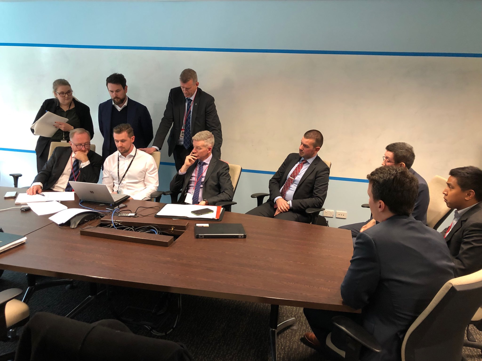 ABC lawyers and AFP officers hover over a computer as they work out what comes within the terms of the warrant. At the end of the table, on the right, are the  ... 			  </div> 			   			  <div class=