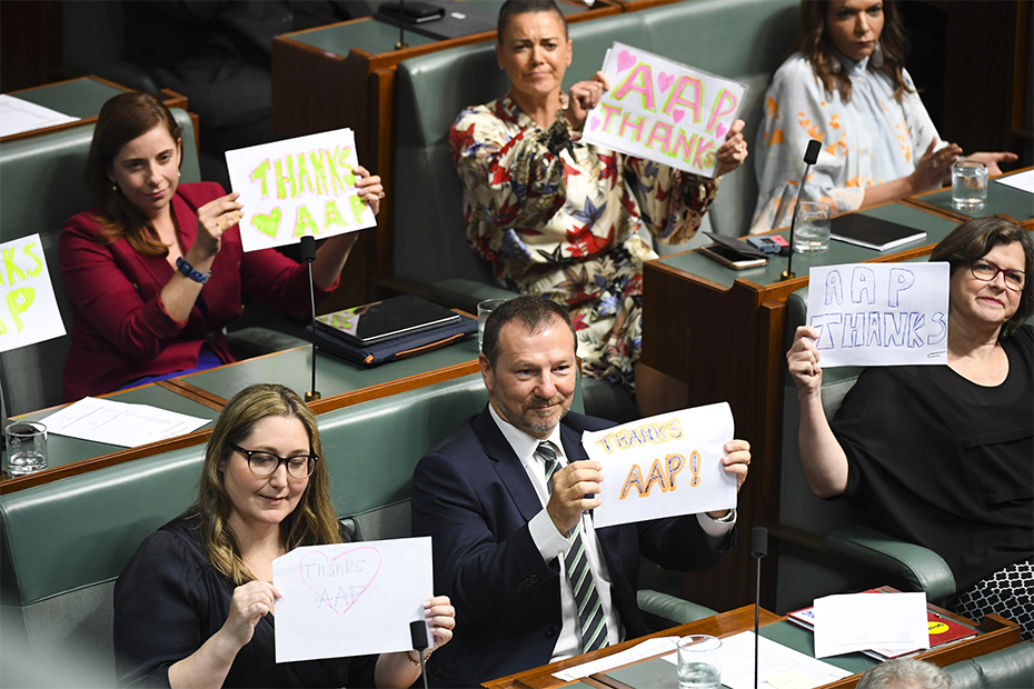 Labor MPs hold up signs in support of Australian Associated Press (AAP) during House of Representatives Question Time at Parliament House in Canberra, Tuesday, 3 March 2020. (AAP Image/Lukas Coch)