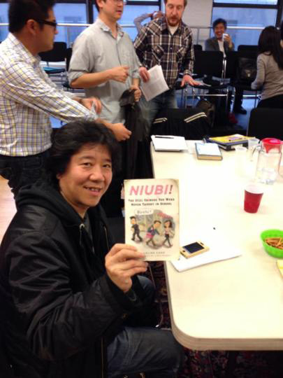 Meng Jingui holding a copy of Niubi by Eveline Chao - photograph by Nick Frisch
