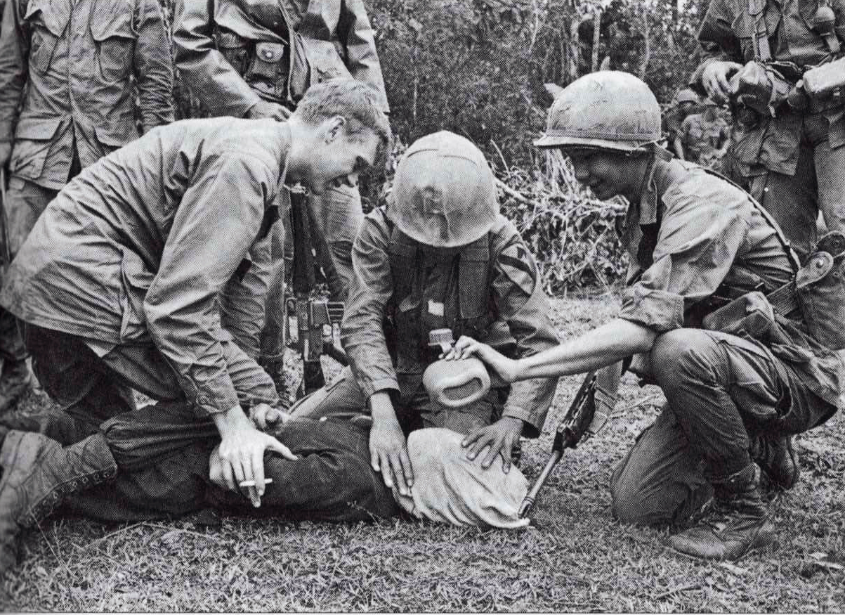 An American soldier, aided by South Vietnamese soldiers, interrogates a suspected Viet Cong insurgent, undated.